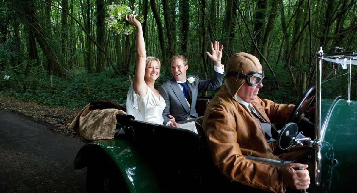 fun vibrant wedding shot of bride and groom in vintage car just married