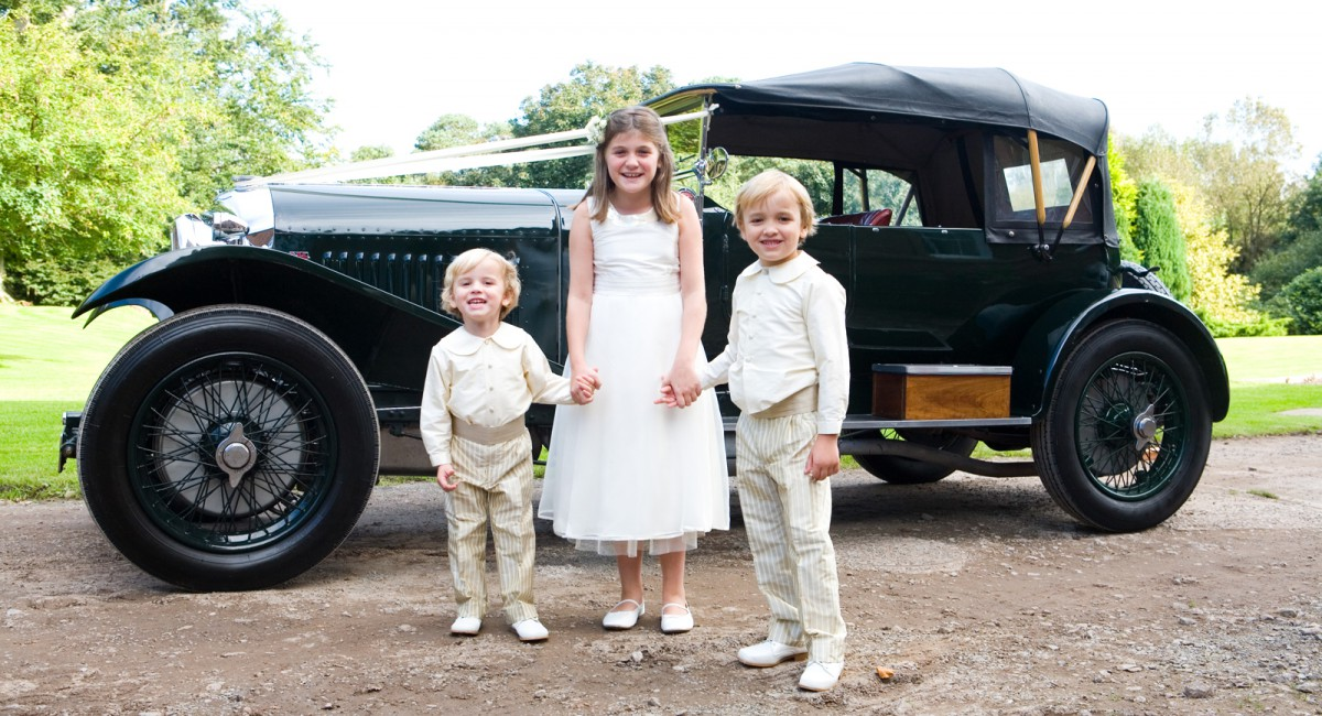 children by vintage car at wedding.