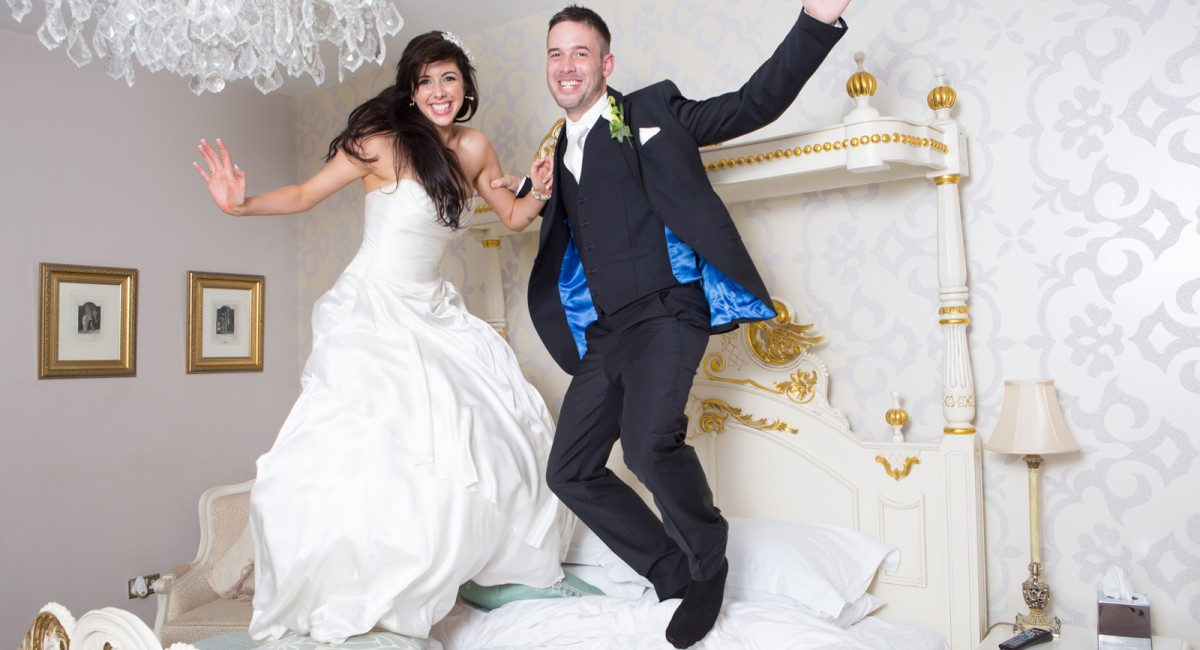 bride and groom jumping on bed